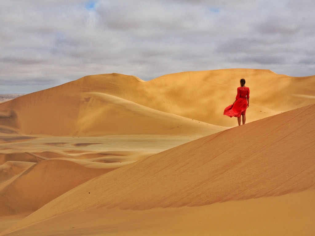 Girl in red dress blowing in the wind on top of Sand Dunes in Dorob National Park