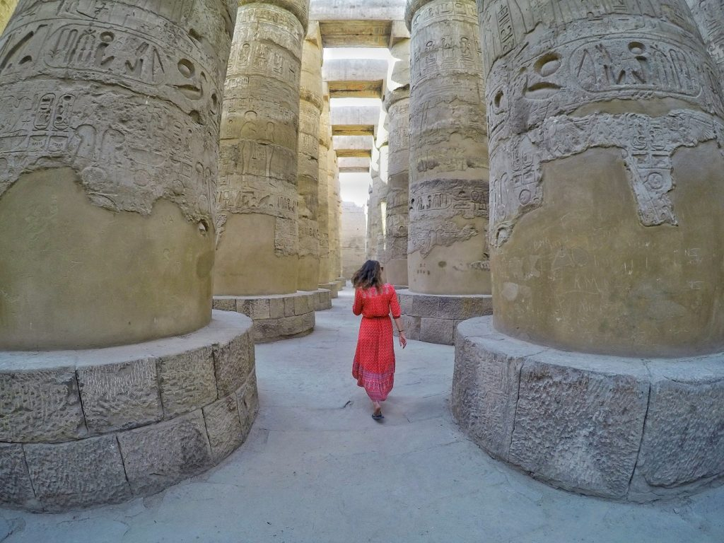 Woman in red dres walking the The Great Hypostle Hall, Karnak Temple