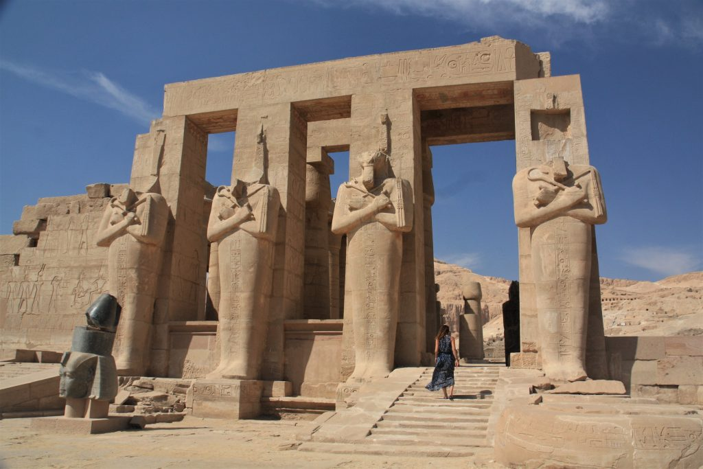 person walk toward Ramesseum with four large structures