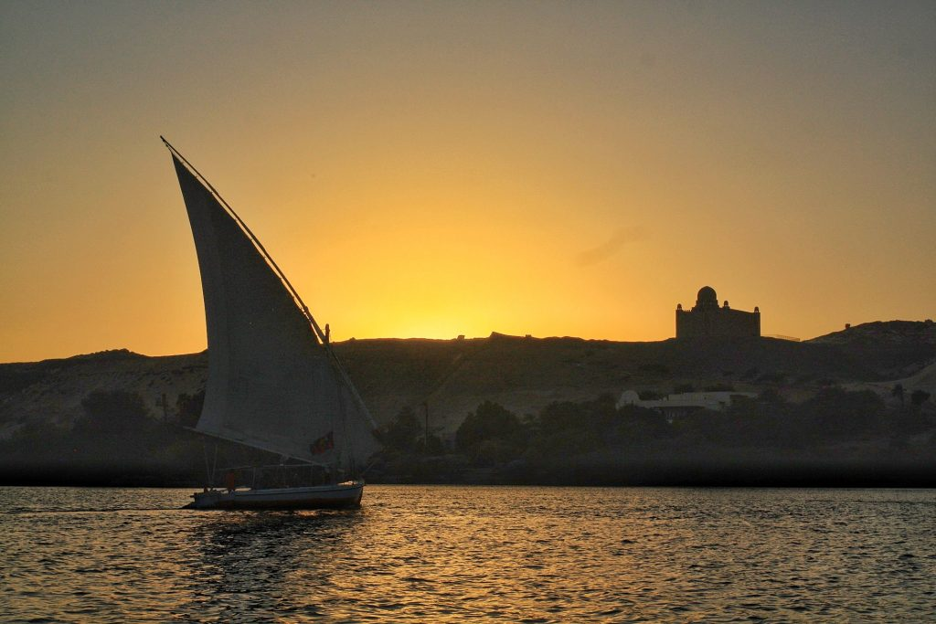 as the sun sets a boat on the water felucca in Aswan