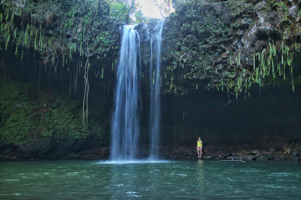 Girl in yellow underneath waterfalls at Twin Falls Maui