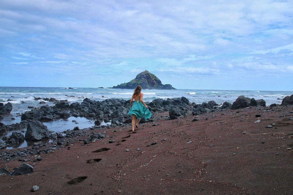 Woman in green flowing dress running on volcanic sand Koki Beach