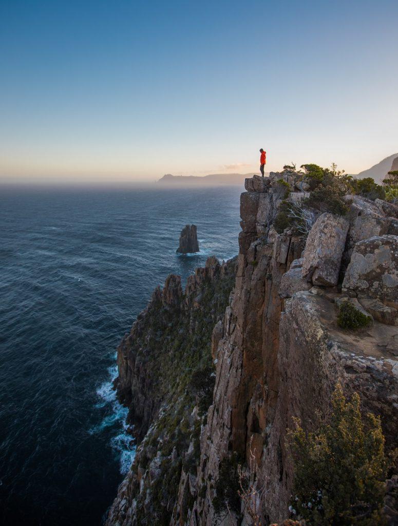 Woman in red jacket on ledge looking down at Tasman Peninsula