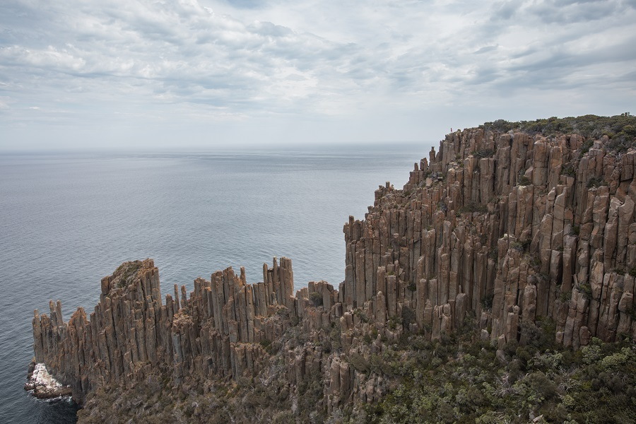 towering rock formation and small human at Cape Raoul