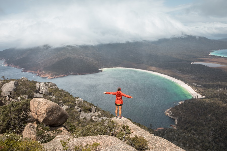 person with hands out at Wineglass Bay from Mount Amos
