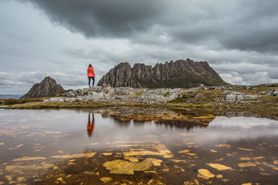 Reflections of cradle mountain and girl