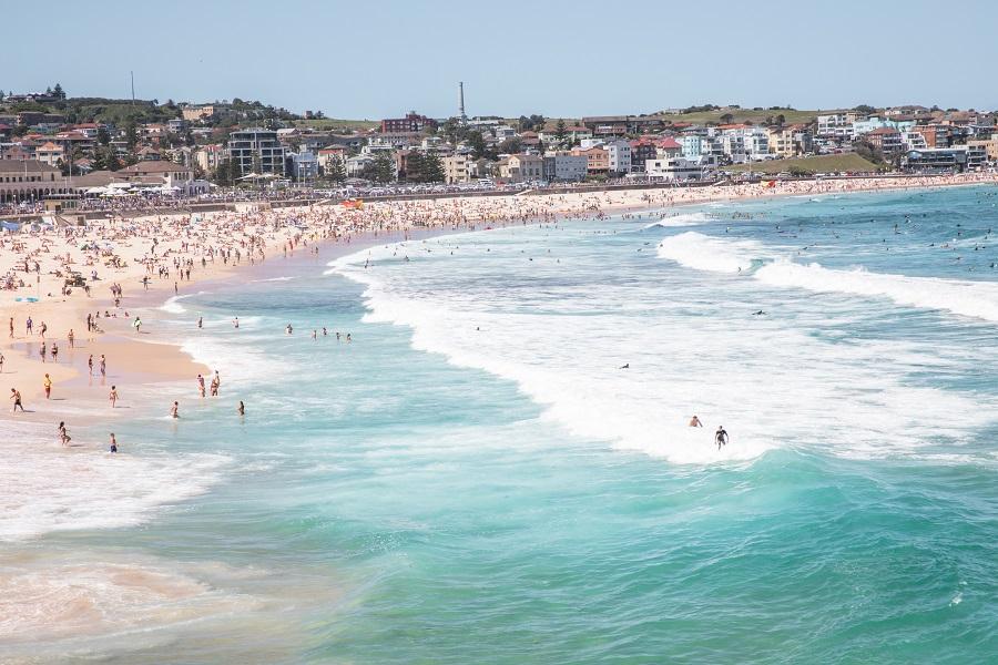 many people and surfers at Bondi Beach