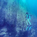 Diver along the Limestone cliff walls in Barracuda Lake, Coron