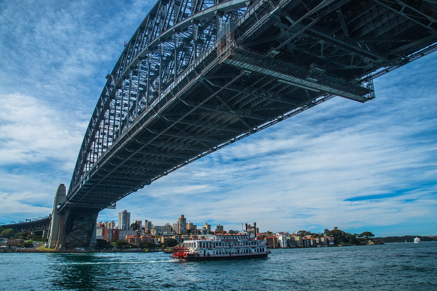 A view from beneath the Sydney Harbour Bridge at the Rocks as a boat passes by.