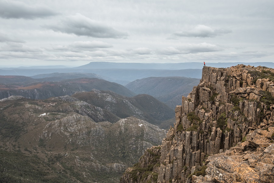 Standing on the edge of a cliff near the summit of Cradle Mountain