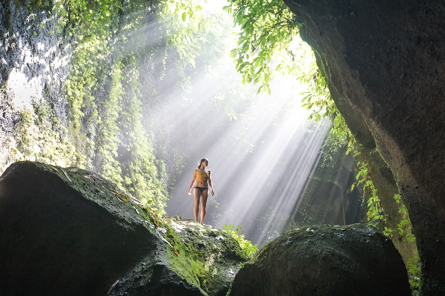 Sun rays and person standing on rock at Tukad Cepung