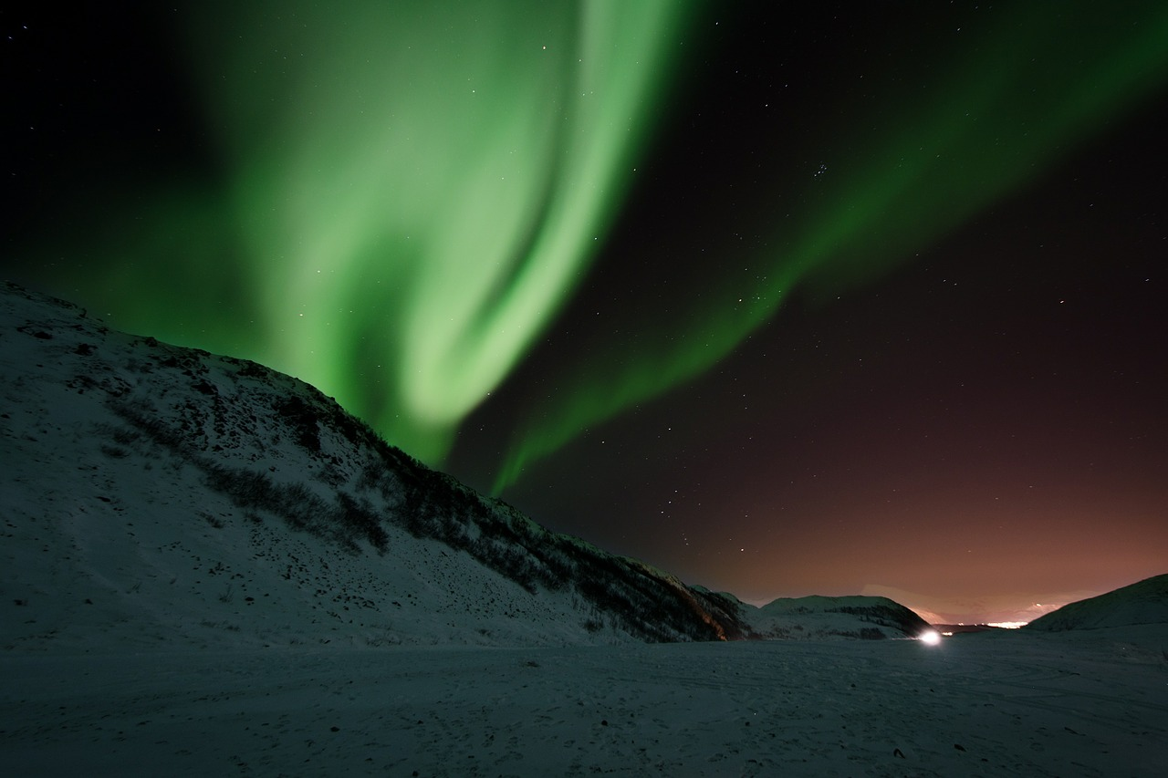 Green aurora borealis in the night sky with snow