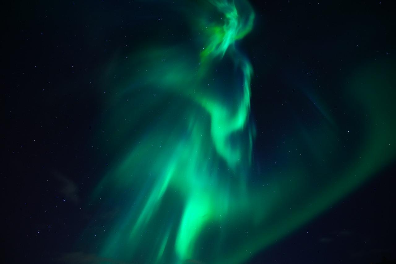turquoise northern lights in dark sky